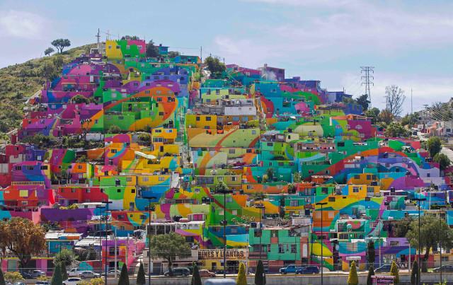 Cientos de casas pintadas con colores brillantes, en lo que los organizadores llaman la pintura mural más grande de México, forman parte de un proyecto auspiciado por el gobierno llamado Pachuca se Pinta, en el barrio Palmitas de Pachuca, México, 30 de julio de 2015.  (AP Foto/Sofia Jaramillo)